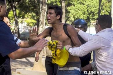 Momento en funcionarios del CICPC detuvieron al estudiante Marco Coello en Plaza Carabobo el 12 de febrero. Un funcionario lo golpea con una extintor de incendio en la espalda.